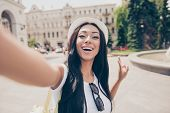 Cute Lady With Bronze Skin And Long Dark Hair, In Cap Is Making A Selfie Shot While Outside In Town. poster