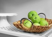 Wicker basket with apples on shelf poster