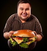 Man eating fast food hamberger. Fat person made great huge hamburger and admires him, intending to e poster