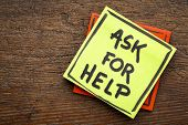 Ask for help advice or reminder - handwriting on a sticky note against rustic wood poster
