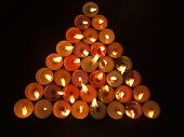 image of flambeau  - bunch of lighted colorful candles on a black background in triangular shape - JPG