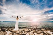 Wedding at the beach. Island wedding. Beautiful bride standing with open arms.  Relaxed woman enjoyi poster