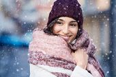 Smiling woman wearing wool bonnet and scarf in a winter cold day. Happy girl in a sweater outdoor in poster