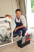 stock photo of washing machine  - Plumber fixing washing machine - JPG