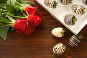 Box with tasty chocolate dipped strawberries and bouquet of flowers on table poster