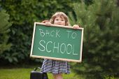 Adorable Smiling Toddler Girl With Back To School Text Blackboard poster