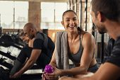 Young woman in conversation with man in gym after workout training. Smiling sweaty girl taking break poster