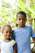 image of creole  - two young children brothers smiling portrait with jungle tropical plants in background Big Corn Island Nicaragua Central America - JPG