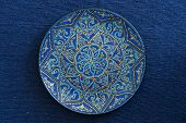 Decorative Ceramic Plate With Blue And Golden Colors, Painted Plate On The Background Of Blue Fabric poster