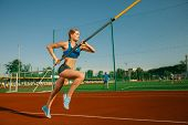 Professional Female High Jumper Training At The Stadium In Sunny Day. Fit Female Model Practicing In poster