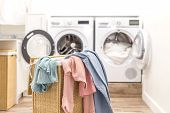 Laundry Basket With Dirty Clothes With Washing And Drying Machines On The Background poster