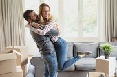 Side view of romantic Caucasian man holding happy Caucasian woman in arms at home poster