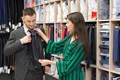 Handsome Gentleman Choosing Cravat In Fashionable Boutique. Girl Assistant Helping Young Man In Styl poster