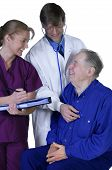 stock photo of medical examination  - Doctor and nurse examining elderly patient friendly exchange - JPG