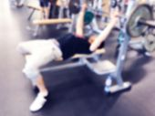 Blurred Background With Man Lifting Barbell Row At Gym. Blur Fitness Gym With People. Gym Equipment poster