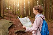 Attractive Energetic Young Lady Holding Map In Both Hands, Looking Attentively At Map, Getting Lost  poster