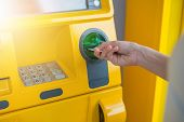 Hand Inserting Atm Card Into Bank Machine To Withdraw Money. poster