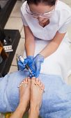 picture of callus  - Nail technician removing callus at feet in nail salon - JPG