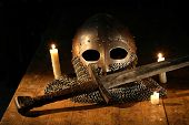 stock photo of knights  - Medieval knight sword and helmet near lighting candles - JPG