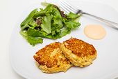 pic of crab-cakes  - Fresh crab cakes on a white plate with sauce and a salad of field greens - JPG