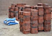 picture of xeriscape  - Stack of red charcoal colored bricks and bags of paving sand stack and ready for construction in desert environment