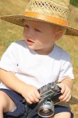 picture of baby cowboy  - a cute baby boy wearing a straw hat is sitting outside playing with a vintage camera - JPG