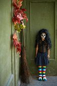 image of antichrist  - Portrait of Halloween girl with broom on background of wall of dilapidated house - JPG