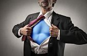 businessman opens shirt and shows superhero suit