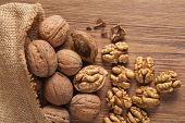 picture of arabian  - Walnut kernels and whole walnuts on rustic old wooden table - JPG