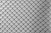 stock photo of chain link fence  - Obsolete gray grunge concrete closed with chain link fence and shadows - JPG