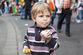 stock photo of funfair  - Little boy of three years eating sweets at a funfair outdoors - JPG