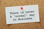 foto of understanding  - There is never a normal day in business typed on a piece of graph paper pinned to a cork notice board - JPG