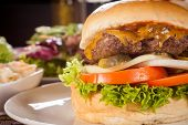 image of ground-beef  - Tasty traditional cheeseburger with a ground beef patty topped with melted cheese and served with onion rings tomato and curly leaf lettuce on a round white bread roll close up view - JPG