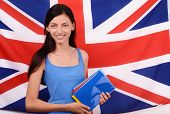Learn English. Beautiful student holding books, blue blank book cover.