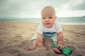 Cute baby sitting on a sand