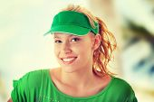 Young beautiful blond woman with green cap