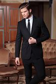 young business man standing in a vintage hotel room and unbuttoning his suit jacket while looking aw