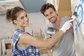 Romantic couple renovating house, painting heart on wall, smiling happy.