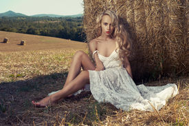 stock photo of haystacks  - Photo of sexy blonde in a field with haystacks - JPG