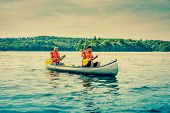 foto of canoe boat man  - Men sailing a canoe in a beautiful lake scenery - JPG