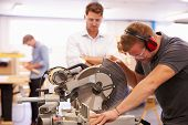 stock photo of carpentry  - Student And Teacher In Carpentry Class Using Circular Saw - JPG