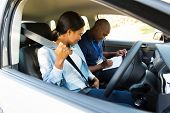 stock photo of seatbelt  - young african girl putting on seatbelt during a driving test - JPG