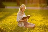 picture of beatitudes  - Blonde girl sitting on the grass and reading a book - JPG