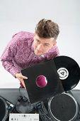 Постер, плакат: Top view portrait of dj showing his vinyl records standing by tu