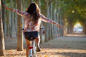 foto of pretty girl  - Outdoor portrait of pretty young girl riding bike in a forest - JPG