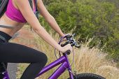 image of riding-crop  - Close up side view of an athletic young woman mountain biking - JPG