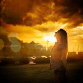 stock photo of independent woman  - Silhouette of Young Woman at Urban Sunset. Dramatic Sky. Toned Instagram Styled Photo. ** Note: Soft Focus at 100%, best at smaller sizes - JPG