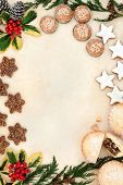 stock photo of biscuits  - Christmas gingerbread biscuit selection and mince pie cakes forming a background border of holly and winter greenery over old parchment paper - JPG
