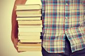image of bookworm  - closeup of a young man holding a pile of books - JPG