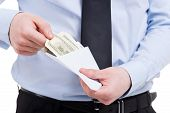 image of white collar crime  - Cropped image of man in shirt and tie taking money from the envelope while standing isolated on white - JPG
